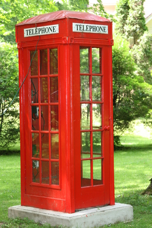 English red telephone booth in park settig Stock Photo