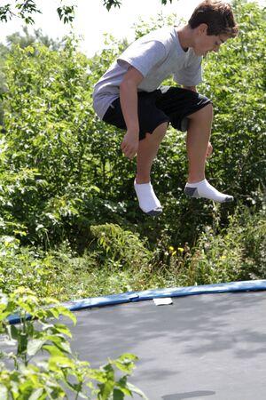 Teen boy bouncing on a trampoline