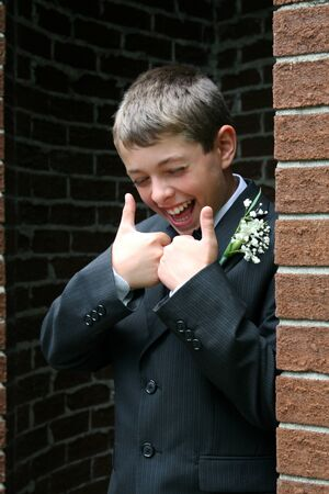 confirmed: Boy, dressed in a formal suit, gives thumbs up