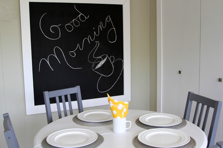 White kitchen table, grey chairs and blackboard says Good Morning