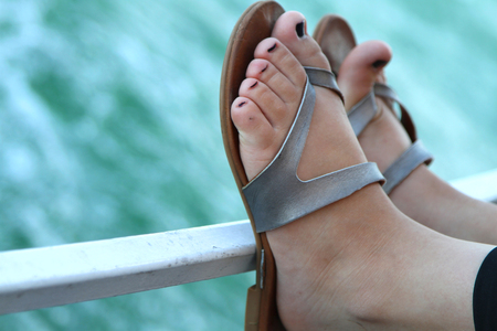 Colorful toes in grey sandals resting on a railing Stock fotó