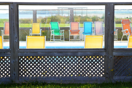 Colorful sun chairs around a pool surrounded by lattice and glass