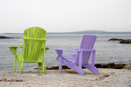 Lime green and mauve adirondack chairs on rocky beach Stock Photo