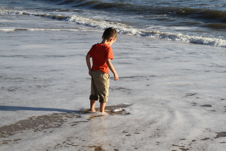 Young boy with pants rolled up,  having fun running in the waves and getting wet in the ocean