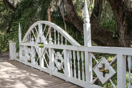 Rustic bridge with white intricate barrier or gate Stock Photo