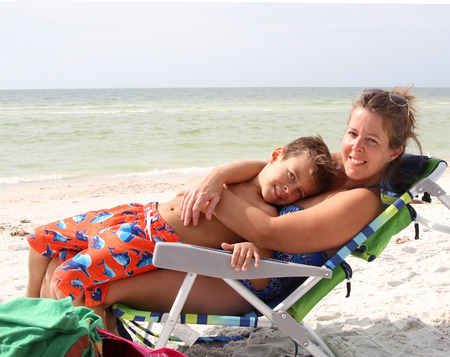 Mother lying and hugging child on a sun chair on a  sandy beach