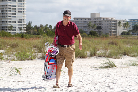Retired male walking on the sand holding beach equipment