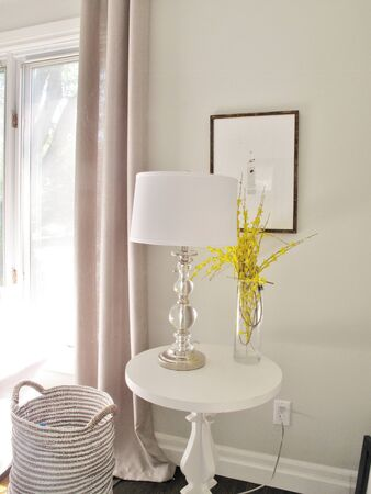 Decorator room with glass ball lamp, white round table, storage basket in white and grey Stock Photo