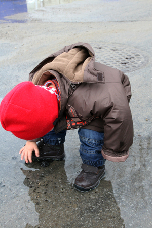 Little boy with red hat playing in the puddle Stock Photo