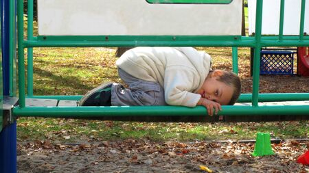 Young boy crouched on top of a  green park structure Stock Photo