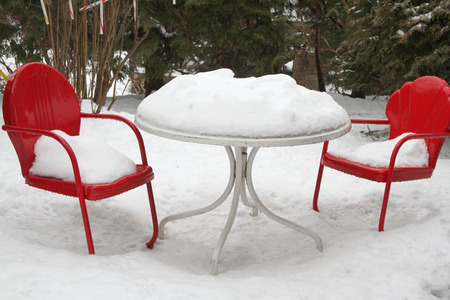 Red metal chairs and white round table in winter snow Stock Photo