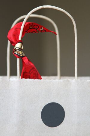 White paper bag grey sticker, red ribbon and handles