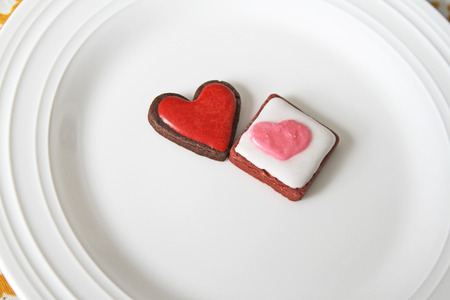 Heart cookies with icing on top on a white plate Stock Photo