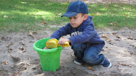 Young boy palying in the sand of a park