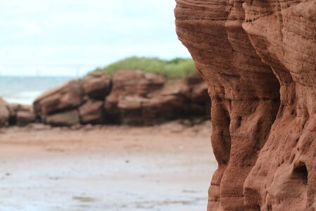 Wind erosion of ruby-red sandstone cliffs and coveted sandy
