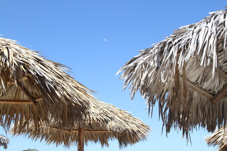 Straw roof of thatched beach umbrella and blue sky Stock Photo