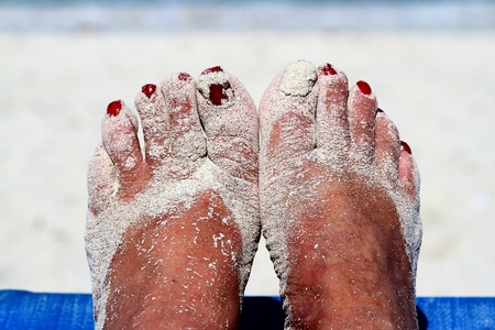 painted toenails: Sandy feet with painted toe nails on the beach