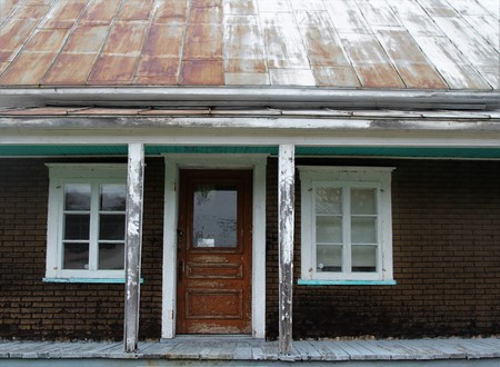Old abandoned house with a tile paper brick walls and rusted empty,metal roof