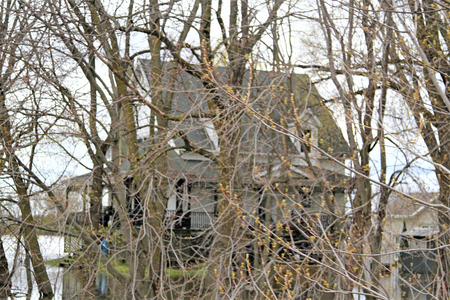 Trees and large house submerged in water Stock Photo