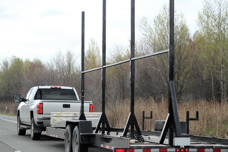White truck pulling a trailer with metal supports for signs Stock Photo