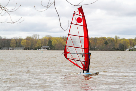 Man on lake windsurfing on a board with a mast