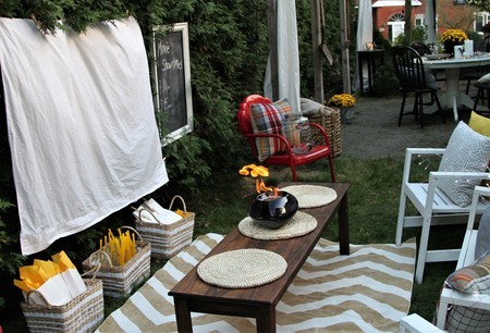 White sheet ready for a movie night outdoors with food and chairs