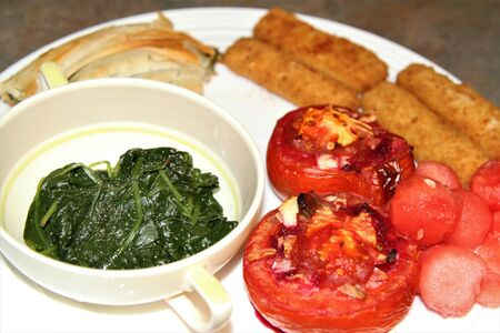 Fish  sticks, spinach, grilled tomatos on a white plates