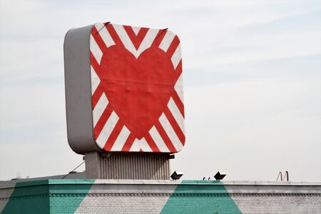 Sign of red heart with background diagonals on top of building Stock Photo