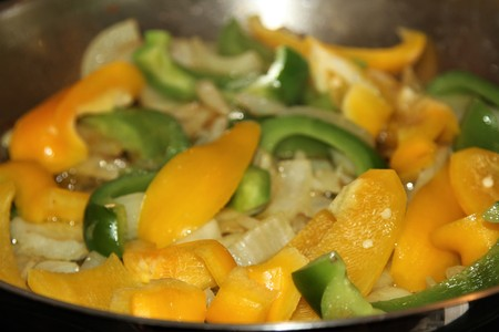 Grilled green and yellow peppers and onion in a stainless steel pan