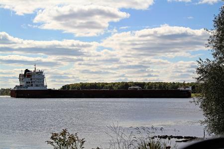 Long cargo ship moving along a waterway