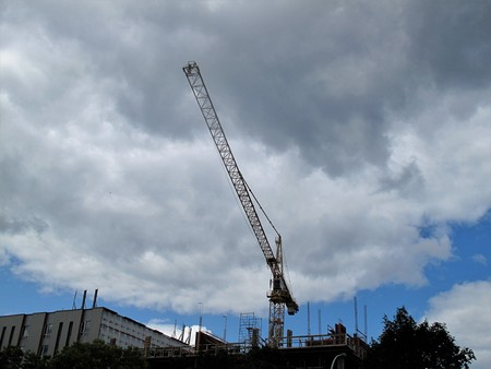 Tall crane with clouds in background Stock Photo