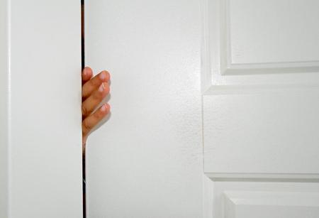Small fingers stuck in the door of a house Stock fotó