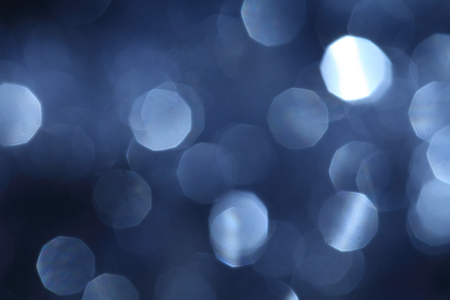 Blue New Year background with blurry spangles for holiday card. A fashionable color palette is Navy Peony. Stock Photo