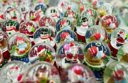 lot of Christmas snow globes with Santa Clauses inside