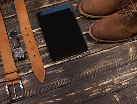 clasp feet: Mens brown clothing and accessories set: boots, leather belt, watch  pc-tablet Stock Photo