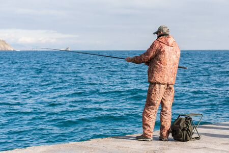 Fisherman standing on pier with fishing rod in hands Stock Photo