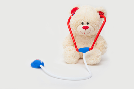 Toy white bear with stethoscope isolated on white