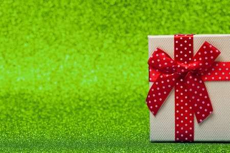 Gift box with red bow on sparkling green background. Bright and festive.