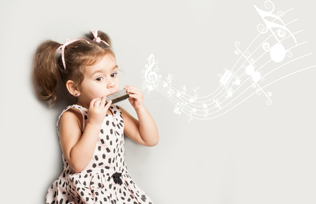 Cute little girl playing harmonica, isolated on white. music education concept