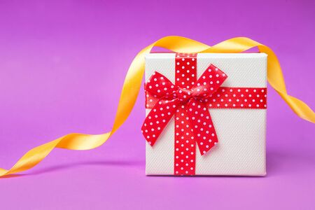 Gift box with red bow on pink and red background. Bright and festive