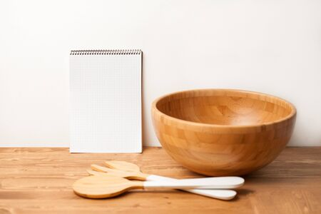 Wooden bowl and cutlery with a notebook on wooden background or table. Natural serving table setting Stock Photo