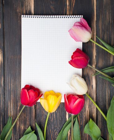 Notebook with Wishlist word on wooden background with spring flowers Tulips. Womans wishlist concept, Close up