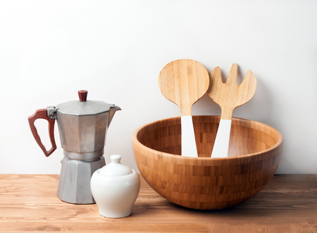 Wooden bowl and cutlery with an Espresso maker on wooden background or table. Natural serving table setting