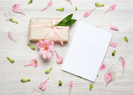 Eco style gift box and greeting card with pink flowers over the wooden background. Top view, flat lay.