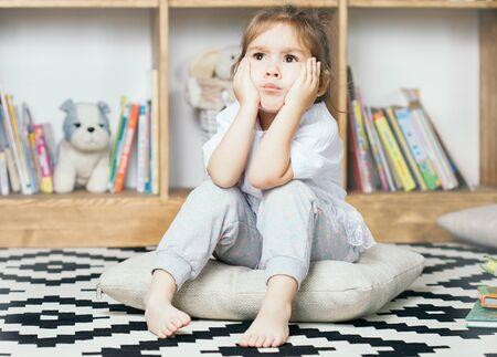 tonto: Linda niña emocional triste por leer libros Foto de archivo