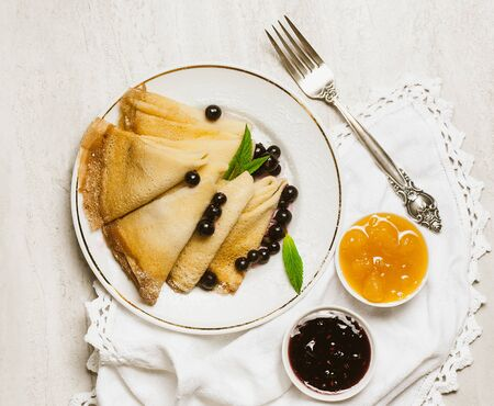 Homemade pancakes with honey, jam and berries with powder sugar Stock Photo