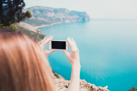 Young smiling woman taking travel photo on trekking excursion day - Hipster girl taking photo at view point with blue ocean background - Concept of healthy lifestyle in beauty of nature. Imagens