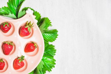 bakground: Strawberries in ceramic bowl on white bakground. Top view, flat lay