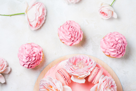 Pink cupcakes with roses and holiday cake. Festive and bright. Wedding Celebration concept.