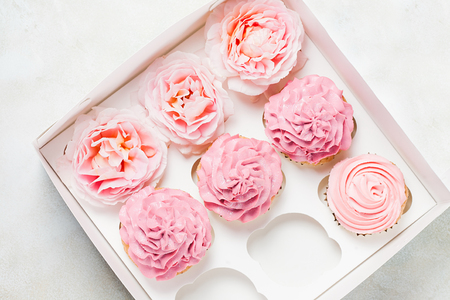 Pink cupcakes with roses in box. Festive and bright. Wedding Celebration concept.
